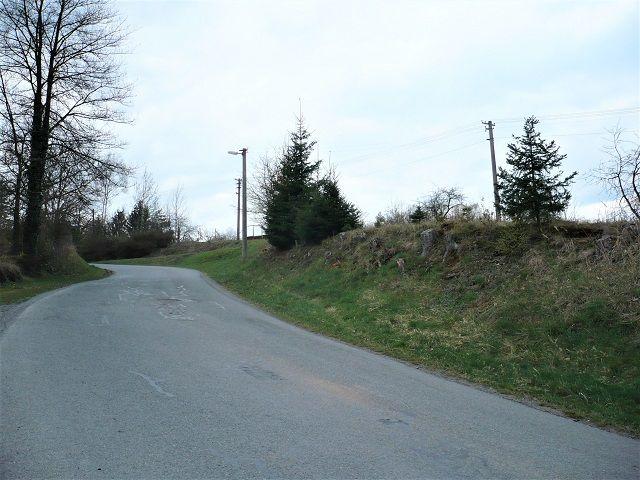 Silnice kolem pozemku směrem z obce